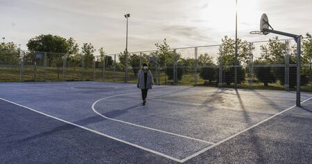 Social distance. Single woman walking around a basketball court maintaining social distance in a state of alarm because of the coronavirus. Coronavirus devices. Social distancing. Protection against pandemics