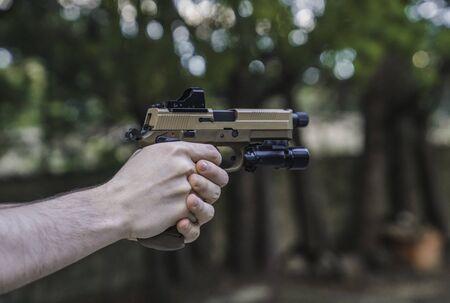 Soldat mit vorgehaltener Waffe. Marine, die Zielübungen tut. FNX Asalto-Pistole. Waffen für den Krieg. Soldat. Marine. Waffenreichweite schneiden. Airsoft. Krieg. Soldat der Infanterie. Asalto-Soldat.