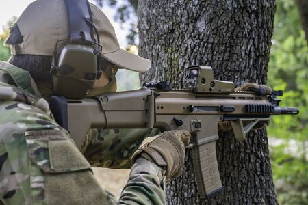 United States Marine with his assault rifle. Airsoft gunner with his assault rifle. Man having fun playing airsoft. Marine doing target practice. Weapons for war. Soldier. Marine. Airsoft. Stock Photo
