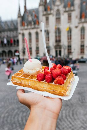 Traditional Belgian dessert. Waffle with strawberry and cream. Belgian waffle brussels food sweet. Grand Market in Brussels, Belgium.The main tourist attraction of the city.