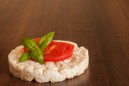 Rice cake (waffle) with tomato slice and green basil leaf on a solid wooden table. A healthy, vegetarian snack. Simple food. Banco de Imagens