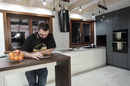 Young caucasian man sitting in kitchen and playing with his mobile.