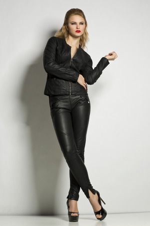 young blond woman in black leather, studio shot