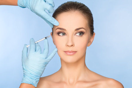 Beauty woman giving botox injections. Banco de Imagens