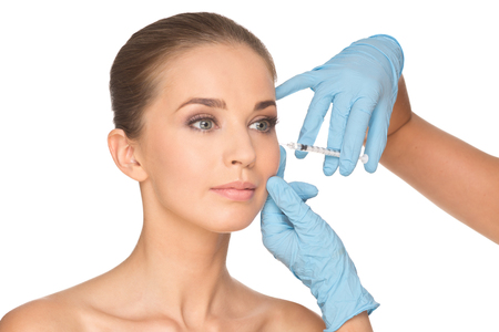 Attractive young woman gets cosmetic injection  , isolated over white background. Doctors hands making an injection in face. Beauty Treatment.