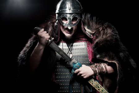 Screaming viking warrior with sword, armour and helmet over black background Stock Photo