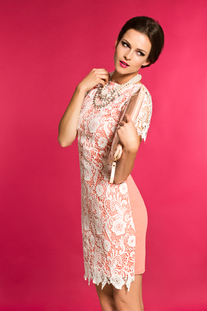 Young woman with pinned hair lacing dress and jewellery and handbag standing over pink background