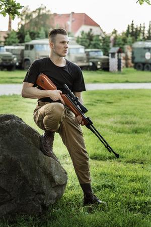 Sentado soldado con pistola. Foto de archivo
