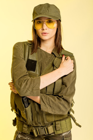 Sexy woman in soldiers suit on yellow background.