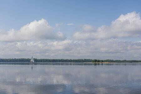 Sail boat on a calm lake Фото со стока