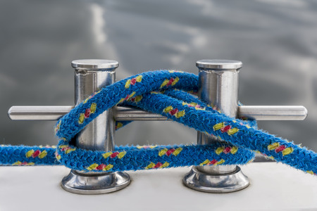 fasten: Blue rope fasten on stake of yacht Stock Photo