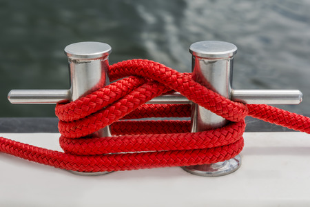 fasten: Red rope fasten on stake of yacht