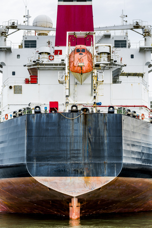 Stern of a container ship with orange life raft Фото со стока