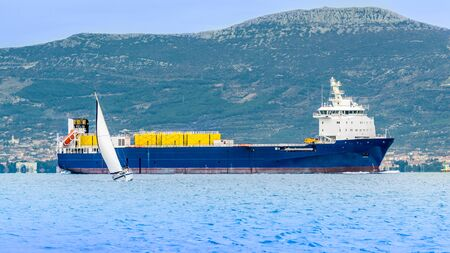 Sailing Yacht in front of Container Ship