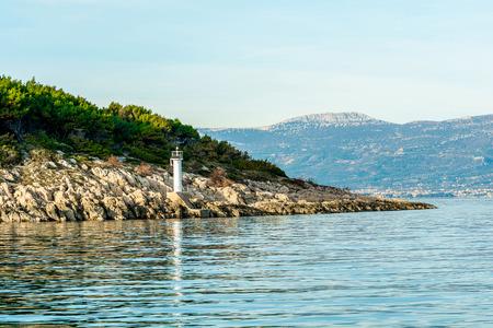 White navigation beacon on a coast Фото со стока