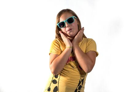 Cheerful girl in sun glasses and yellow shirt on white background