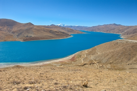 Yamdrok Tso, or Turquoise lake,at 4441 m altitude, is one of the holliest lakes of Tibet; Mt  Nojin Kangtsang in the distance photo