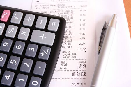 outgoings: business concept with calculator and bill Stock Photo