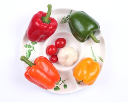 Four colorful peppers, small tomatoes and garlic on white plate photo