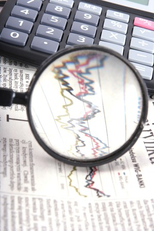 magnifying glass over financial graph photo