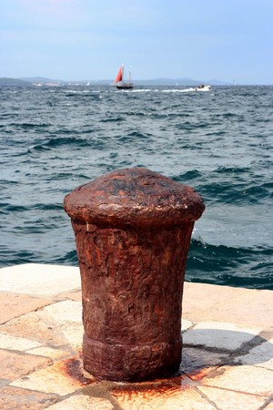 Ship pier (bollard)  with rusty mooring with sea view photo