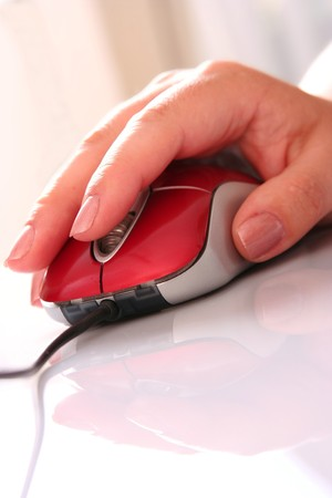 Computer red mouse and female hand with reflection   photo