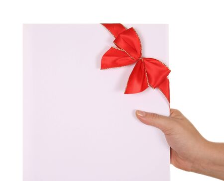 Paper card with red ribbon in woman hand isolated on white background photo