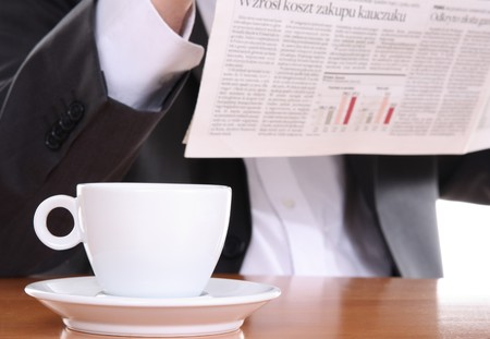 coffeebreak: Businessman reading newspaper and drinking coffee, business break at office Stock Photo