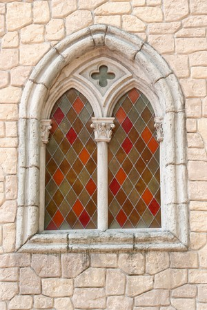 gothic design: colour stained glass window in stoned church