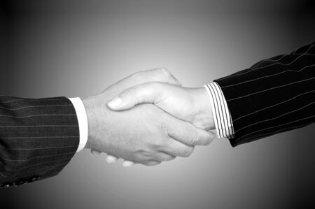 black handshake: Business handshake (man with woman) o gray tone background Stock Photo