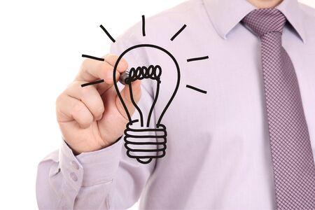 Businessman drawing light bulb on white-board