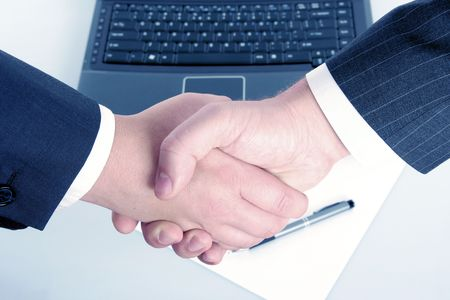man and woman shaking hands in front of computer and document with pen   photo