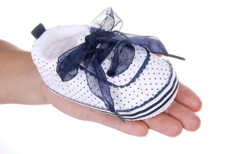 Shoe for infant on woman hand  photo