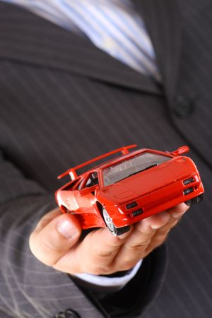 Businessman handing over a new red sport toy car photo