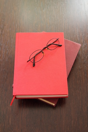 Eyeglasses and two red books laying on wood table photo
