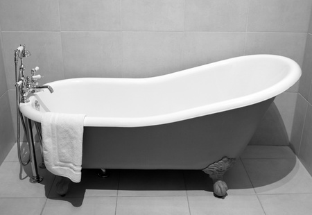 bathtubs: Old style bath tub with metal legs and towel, vintage style on b&w tone