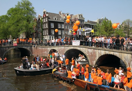 Amsterdam, Netherlands, April, 30, 2011, people dressed in orange celebrate Queens Day on boats and streets Editorial