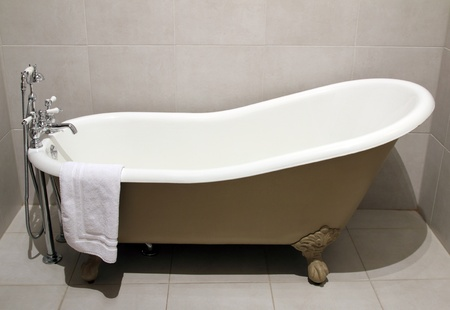 Old style bath tub with metal legs and towel, vintage style Stock Photo
