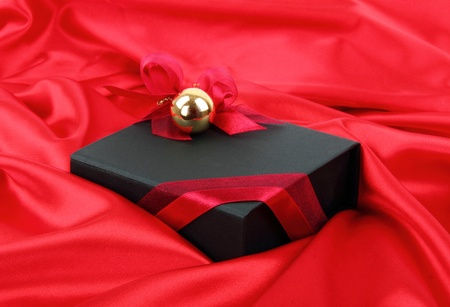 Black elegant gift box with gold bauble on red satin background photo