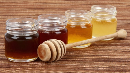 four jars full of honey wooden drizzler, mix taste Archivio Fotografico