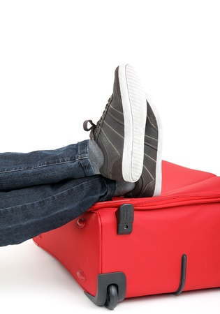 Legs of a young man lies on the red suitcase photo