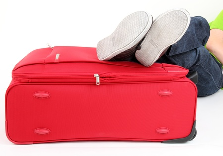 journeying: Legs of a young man lies on the red suitcase