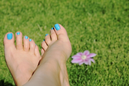 woman foot with blue nails on grass background with flower
