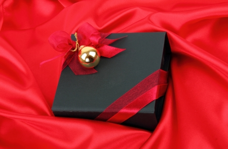 Black gift box with gold bauble on red satin background photo