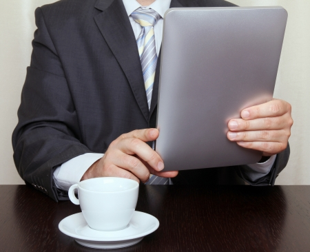 Businessman reading news on tablet and drinking coffee photo