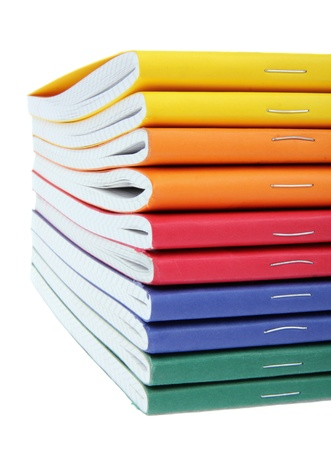 multicolored exercise books over the white background, close up  photo