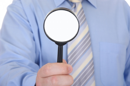 Magnifying Glass in the hand of businessman - focus on magnifying photo