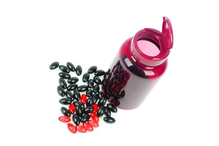 Red and black pills spilled around a pill bottle photo
