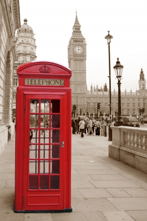 A traditional red phone booth in London with the Big Ben in a sepia background photo
