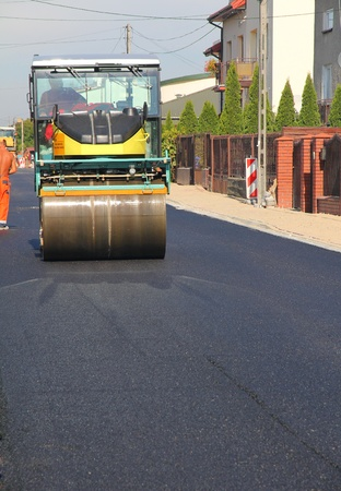 Road roller at a road , driving on fresh asphalt photo